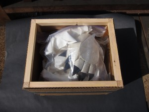 Reinforced thin cardboard box with wood strips by Donald Moss. Plastic bags containing origami models loosely packed inside it.